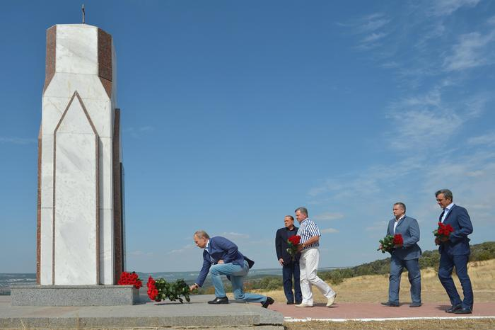 Russian President Vladimir Putin, left, and former Italian Prime Minister Silvio Berlusconi, second left, lay flowers at a memorial to the soldiers from Sardinia killed in the Crimean War, near Mount Gasfort outside Sevastopol in Crimea, Friday, Sept. 11, 2015. From right, Sevastopol mayor Sergei Menyailo, Crimean leader Sergei Aksyonov and Presidential Envoy to Crime Oleg Belaventsev. (Alexei Druzhinin/RIA-Novosti, Kremlin Pool Photo via AP)